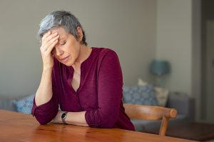 Retired woman looking upset sitting at table | Counseling for life transitions and empty nest syndrome | Therapy & Counseling in Houston, TX | Natalie Mica LPC | 77006