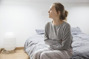 Tired Sick woman wearing grey sweats and sitting on her bed   Therapy for depression   Natalie Mica LPC   77006