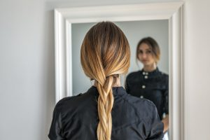 Woman with braided hair standing in front of the mirror looking at herself | Body image and eating disorders | Natalie Mica LPC | 77006