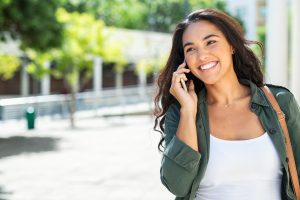 Happy young woman talking on the phone and smiling in downtown Houston, TX | Depression counseling | Natalie Mica LPC | 77006