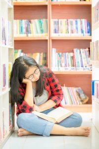 Teenage girl reading book in a library | Counseling for body image | Eating Disorder treatment & therapy for eating disorders houston, tx | therapist in Houston Texas | Natalie Mica | 77006