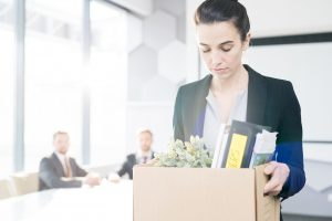 Woman carrying box of personal items after quitting her job | Counseling for Life Transitions including empty nest syndrome, retirement and college graduation | Houston Therapist 77006