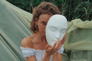 Woman hiding behind a mask. This represents how women with perfectionism often feel fear and anxiety about being accepted and valued as themself. I am a counselor in Houston TX 77006 who provides therapy for perfectionists to help them with anxiety, stress management, and shame.