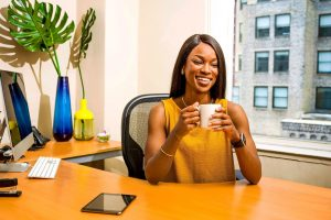 Happy African American woman in yellow shirt drinking coffee in her office. This represents how therapy for perfectionists can help women with perfectionism accept themselves and heal from stress, anxiety, depression, shame, and fear. I am a counselor in Houston TX 77006