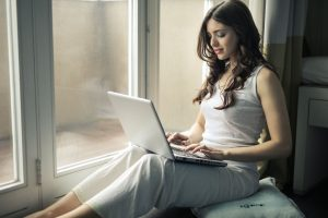 young adult woman with depression and anxiety at home in white pants and camisole during a session of online therapy in Texas   Houston Therapist   Natalie Mica LPC   Counseling  77006