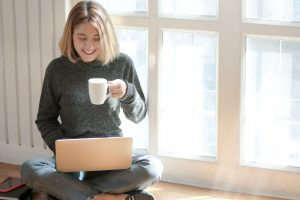 Teen girl in jeans and a sweater sitting on the floor at home drinking coffee and smiling because online therapy in Texas has healed her depression and anxiety | Houston Counselor | Natalie Mica LPC | 77006